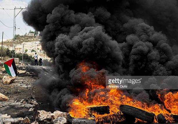 Israeli-Palestinian conflict. Palestinian flag near burning tyres. Clashes between Palestinian demonstrators and the Israeli army at Kafr Qaddum . In...