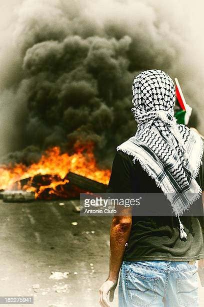 Israeli-Palestinian conflict. Palestinian protester standing near burning tyres. Clashes between Palestinian demonstrators and the Israeli army at...