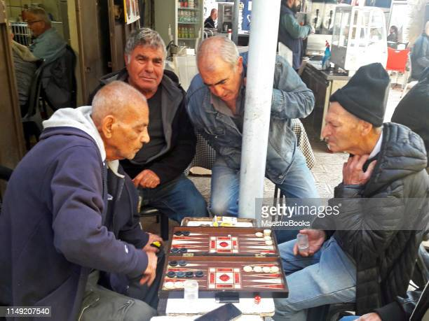 israelis and arab men playing backgammon together in the streets of jerusalem. - israeli ethnicity stock pictures, royalty-free photos & images