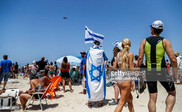 Israelis and tourists watch an air show during the festivities of the 70th Independence Day on April 19 2018 in the Mediterranean coastal city of Tel...