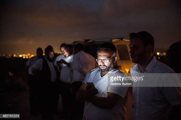 Israelis check their cell phones while waiting for outgoing rocket fire or Israeli airstrikes from a hill overlooking the Gaza Strip on July 14, 2014...