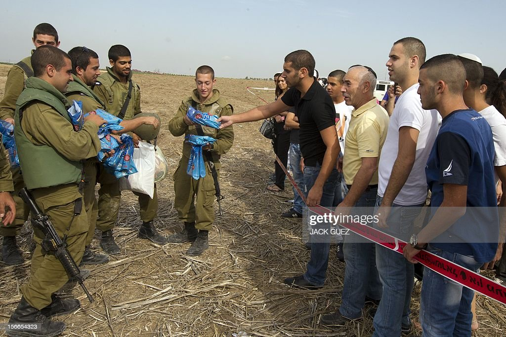 Israelis come to support and gives presents to soldiers in the city of Ashdod on November 18, 2012, on the fifth day of Israel's bombadment of the Palestinian Gaza Strip. Israel's Foreign Minister Avigdor Lieberman said that Israel would not negotiate a truce with Gaza Strip's Hamas rulers as long as rocket fire continues from the Palestinian enclave.