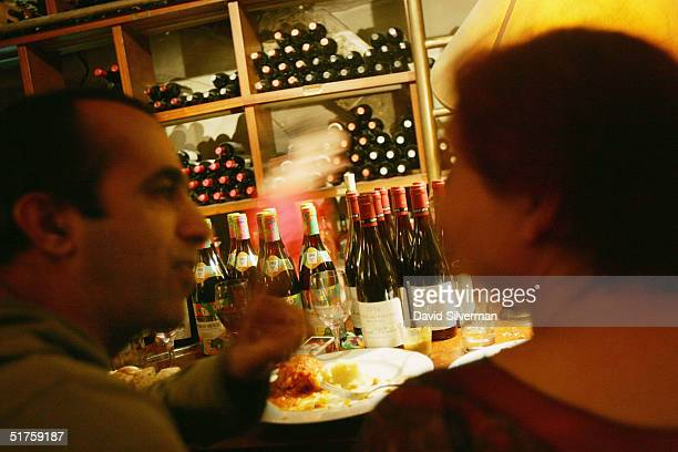 Israelis eat at the bar covered with bottles of Beaujolais Nouveau 2004 at Yoezer Wine Bar after midnight on November 18 2004 in Tel Aviv In Israel...