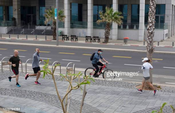 Israelis exercise on the beach promenade on May 9, 2020 in Tel Aviv, Israel. Israel is preparing to reopen markets and shopping malls across the...