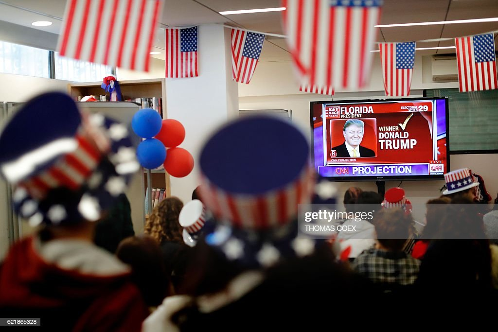 TOPSHOT - Israelis follow the US presidential elections on TV at the American Center in Jerusalem on November 9, 2016. Billionaire populist Donald Trump, tapping into an electorate fed up with Washington insiders, was on the verge of a shock victory Wednesday over Hillary Clinton in a historic US presidential election that sent world markets into meltdown. COEX