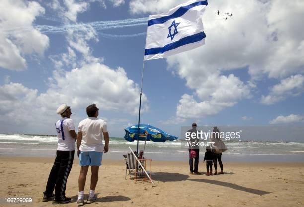 Israelis gather on the beach in the Mediterranean coastal city of Tel Aviv as they watch a military air show marking the 65th anniversary of Israels...