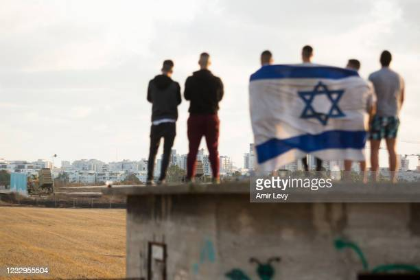 Israelis gather to watch the Iron Dome missile defence system launch to intercept rockets fire from the Gaza Strip on May 17, 2021 in Ashdod, Israel....