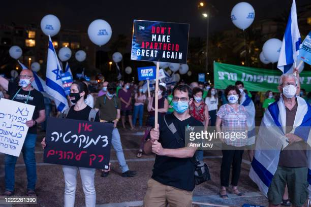 Israelis hold signs as they protest against the Israeli goverment's plan to annex parts of the West Bank on June 23, 2020 in Tel Aviv, Israel....