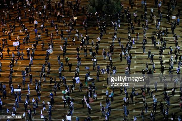 """Israelis, keeping at a safe distance from one another, take part in a """"Black Flag"""" demonstration, to protest against Prime Minister Benjamin..."""