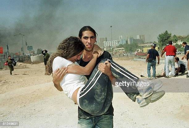 Israelis leave the scene of twin suicide bombings of two buses 31 August 2004 in the southern Israeli town of Beersheva At least 15 people were...