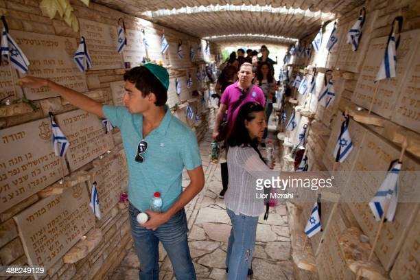 Israelis light candles at a commemorative plaque devoted to fallen soldiers at the military cemetery on May 5 2014 in Jerusalem Israel Israel marks...