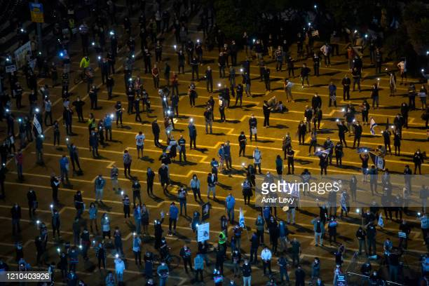 Israelis light flash lights as they protest at a rally in Rabin Square on April 19, 2020 in Tel Aviv, Israel. Thousands of Israelis gather at an...