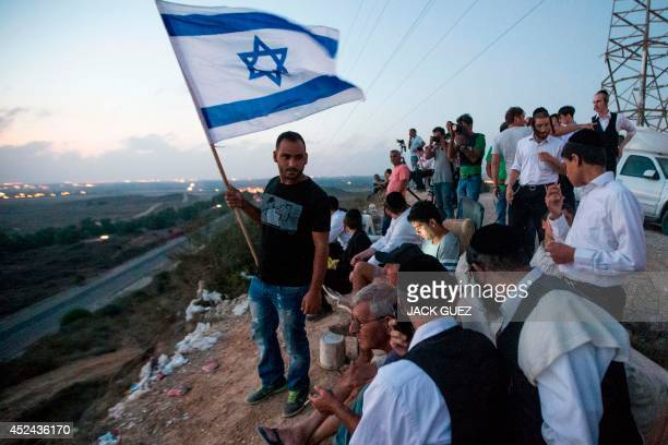 Israelis, mostly residents of the southern Israeli city of Sderot, stand with an Israeli flag on a hill overlooking the Gaza Strip, on July 20 to...