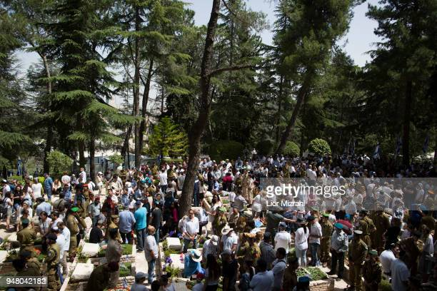 Israelis observe two minutes of silence near graves as a siren is heard across the country at the military cemetery on April 18 2018 in Jerusalem...