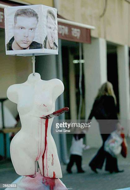 Israelis pass by the work by Israeli artist Pyotr Podovni January 20 2004 in Tel Aviv Israel which includes a portrait of Mijailo Mijailovic the...