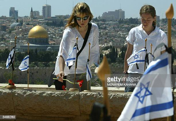 Israelis place flowers over the graves of Israeli soldiers killed during the 1948 war on the Mount of Olives military cemetery overlooking the Dome...