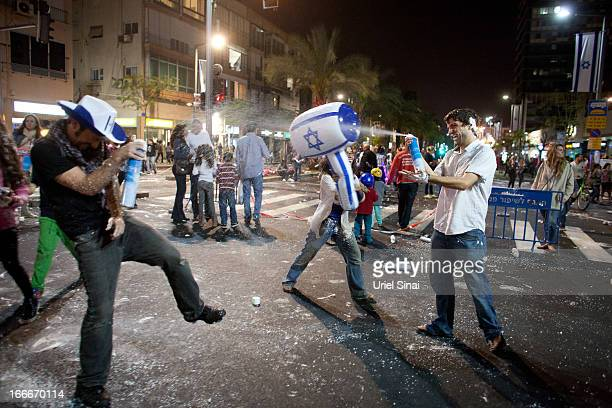 Israelis play with foam spray as they celebrate the Jewish state's 65th Independence Day on April 15 2013 in Tel Aviv Israel