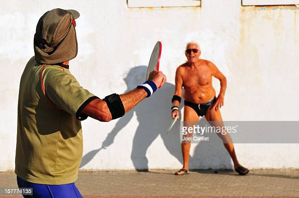 two men playing matkot in israel - old man in speedo stock photos and pictures