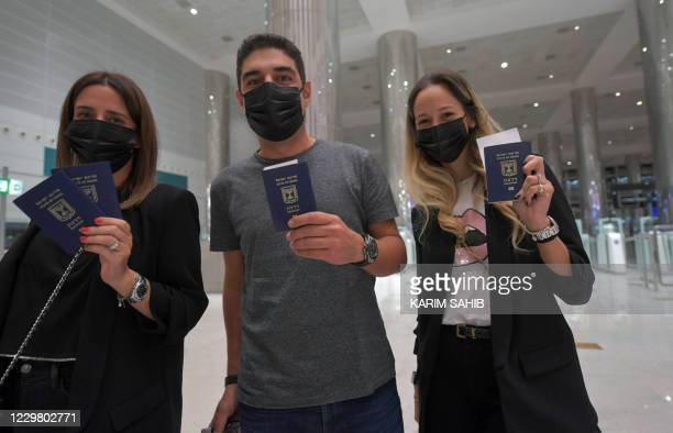 Israelis pose for a picture with their passports upon arrival from Tel Aviv to the Dubai airport in the United Arab Emirates, on November 26 on the...