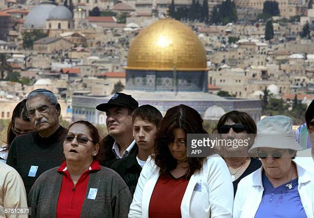 Israelis relatives of fallen soldiers observe two minutes of silence during a memorial ceremoney for slain soldiers at the military cemetery on the...