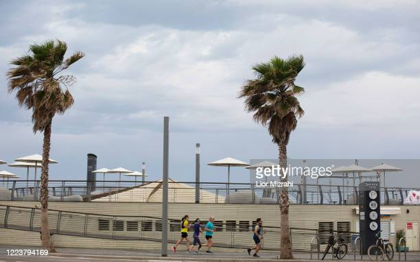 Israelis run on the beach promenade on May 9, 2020 in Tel Aviv, Israel. Israel is preparing to reopen markets and shopping malls across the country...