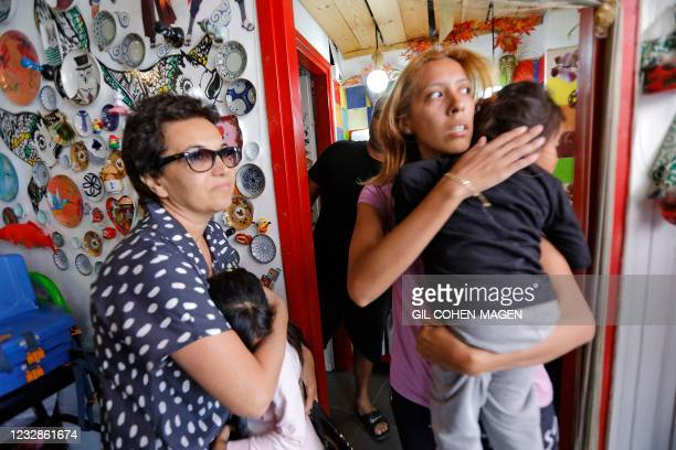Israelis take cover in a shop as a siren rings during an attack of rockets from the Hamas-controlled Gaza Strip into Israel, on May 13 in the...