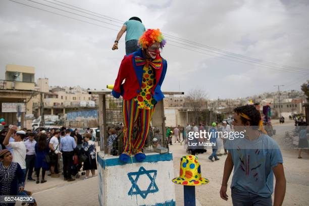 Israelis take part in a parade celebrating the Jewish holiday of Purim on March 12 2017 in Hebron West Bank Purim celebrates the miraculous salvation...
