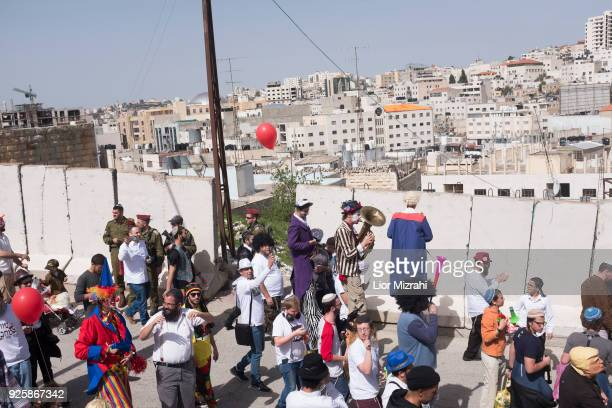 Israelis take part in a parade celebrating the Jewish holiday of Purim on March 1 2018 in Hebron West Bank The carnivallike Purim holiday is...