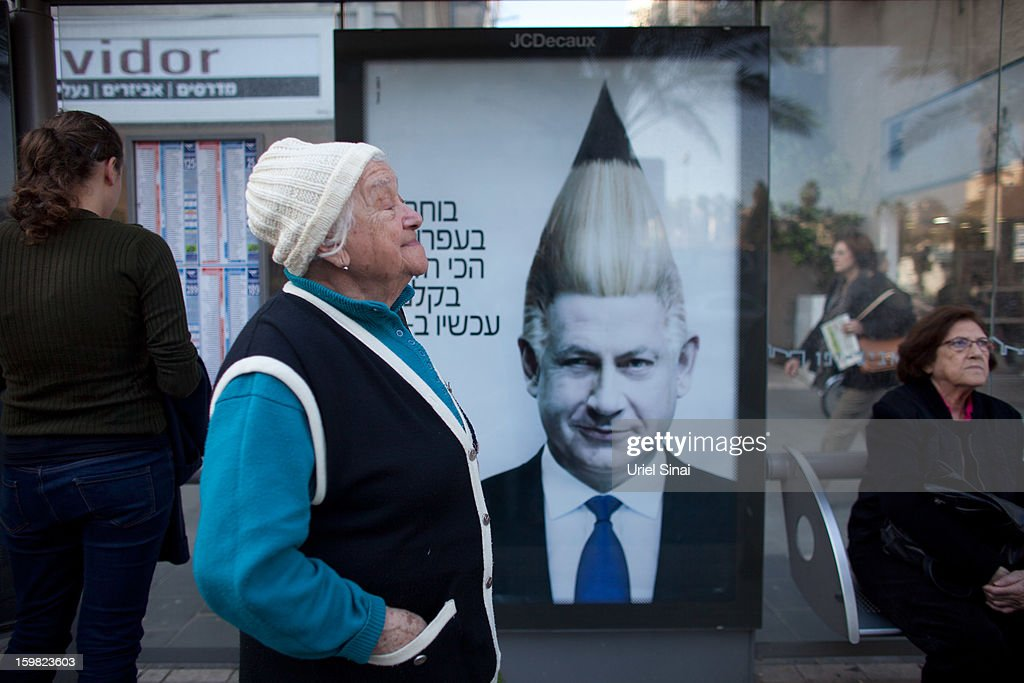 Israelis wait for the bus as a commercial poster for an Israeli school displaying the manipulated image of Israeli Prime Minister Benjamin Netanyahu on a bus stop on January 21, 2013 in Tel Aviv, Israel. Israeli elections are scheduled for January 22 and so far showing a majority for the Israeli right.