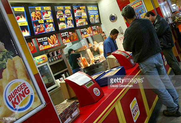 Israelis wait under Hebrewlanguage menus for their meals at a Burger King restaurant February 7 2003 in the central Israeli town of Petah Tikva a day...