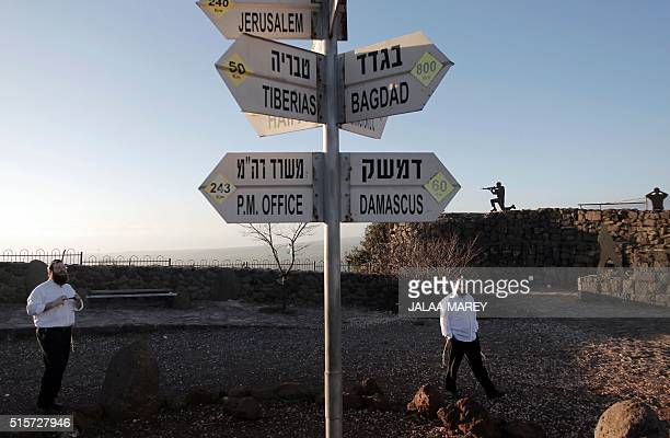 Israelis walk near a sign for tourists showing the distance to Damascus and Baghdad among other destinations at an army post on Mount Bental in the...
