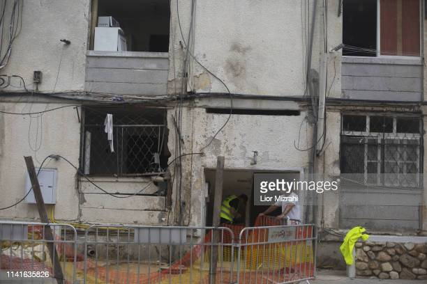 Israelis walk next to building on that was damaged by a rocket strike from the Gaza Strip on May 6 2019 in Ashkelon Israel Palestinian leaders in...