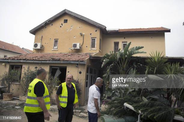 Israelis walk next to house on that was damaged by a rocket strike from the Gaza Strip on May 6 2019 in Ashkelon Israel Palestinian leaders in Gaza...