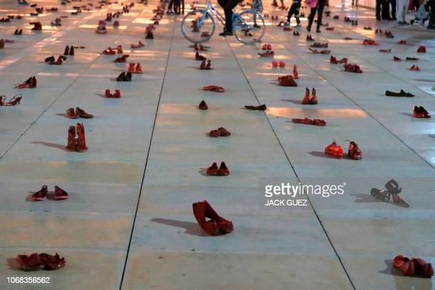 Israelis walk past an installation of red shoes during a rally against domestic violence in the Israeli coastal city of Tel Aviv on December 4 2018...
