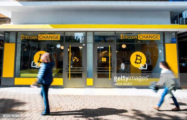 Israelis walk past the cryptocurrency 'Bitcoin Change' shop in the Israeli city of Tel Aviv on January 17 2018 At the end of 2017 Israel Securities...