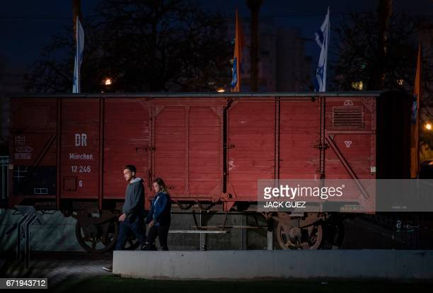 Israelis walk past train wagon used in Nazi Germany to transport Jews to concentration camps in the Israeli coastal city of Netanya on April 23 as...