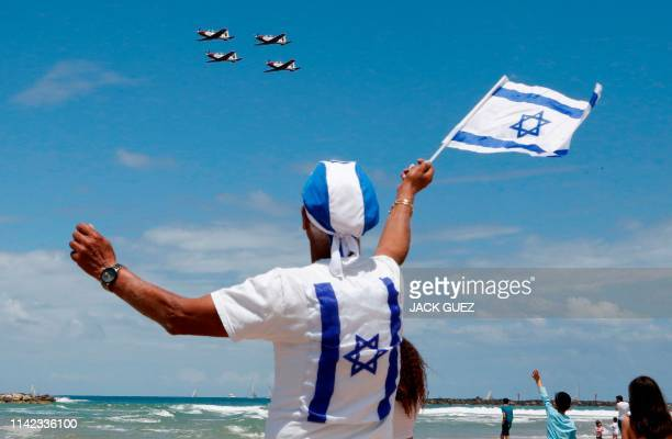 Israelis watch while Efroni T6 Texan II planes perform during an air show over the beach in the Mediterranean coastal city of Tel Aviv on May 9 2019...