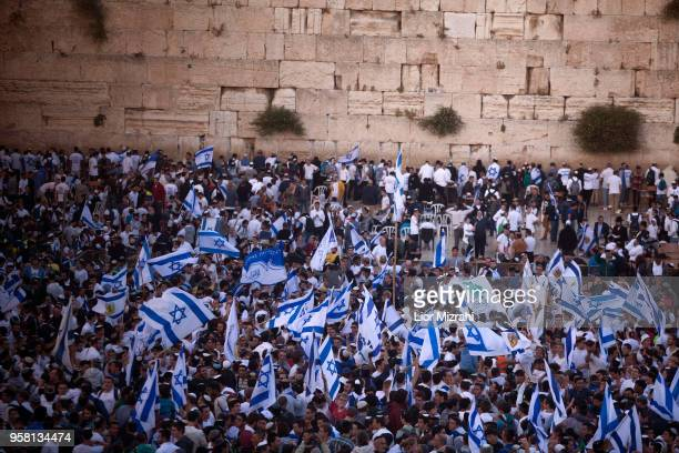 Israelis wave their national flags during a march at the Western Wall on May 13 2018 in Jerusalem Israel Israel mark Jerusalem Day celebrations the...