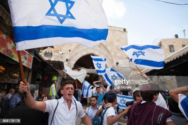 Israelis wave their national flags during a march inside Damascus Gate on May 13 2018 in Jerusalem Israel Israel mark Jerusalem Day celebrations the...