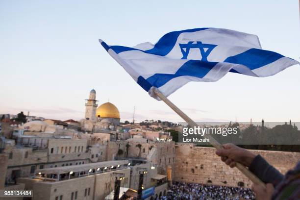 Israelis wave their national flags during a march next to the Western Wall on May 13, 2018 in Jerusalem, Israel. Israel mark Jerusalem Day...