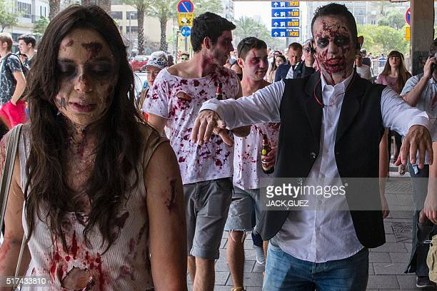 Israelis wearing costumes take part in a Zombie walk in the city of Tel Aviv as part of the Jewish holiday of Purim on March 25 2016 The carnivallike...