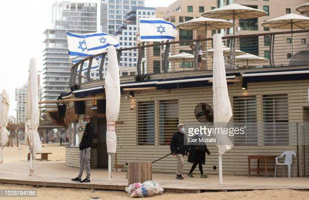 Israelis wearing protective masks walk on the beach promenade on May 9, 2020 in Tel Aviv, Israel. Israel is preparing to reopen markets and shopping...