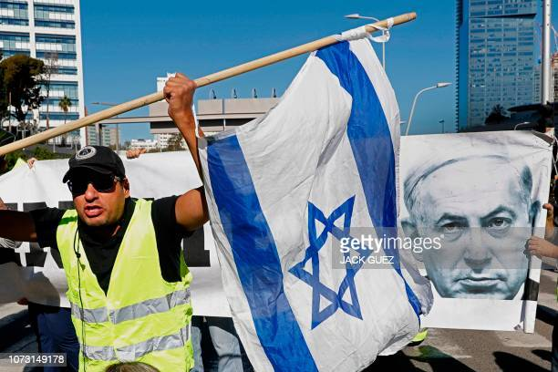 TOPSHOT Israelis wearing yellow vests carry their national flag and a picture of Prime Minister Benjamin Netanyahu as they demonstrate against the...
