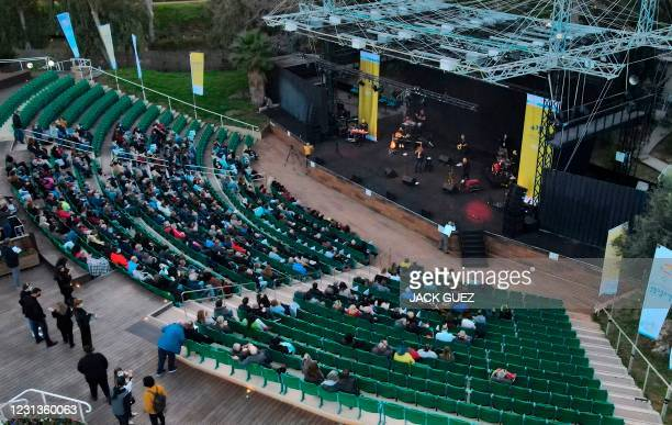 """Israelis who were allowed to enter an arena after showing their """"green pass"""" attend a Green Pass concert for vaccinated seniors, organised by the..."""