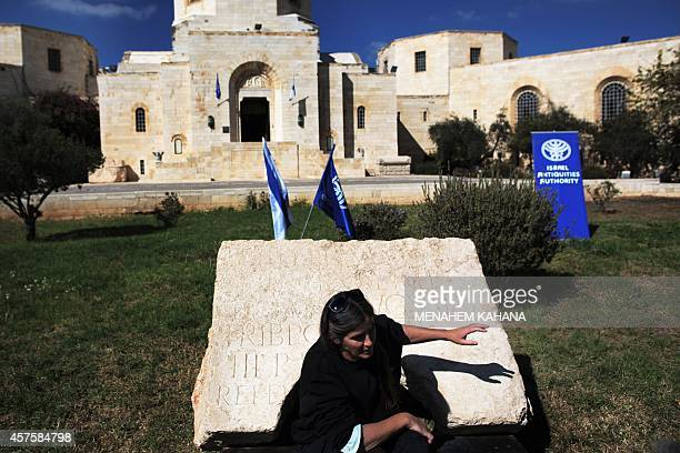 Israel's Antiquities Authority staff Rina Avner displays a 2000yearold commemorative stone inscription dedicated by the Roman army to Roman Emperor...