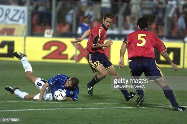 Israel's Avi Nimny falls during action with Spain's Ivan Helguera and Miguel Angel Nadal during their group 7 World Cup 2002 qualifying match in...