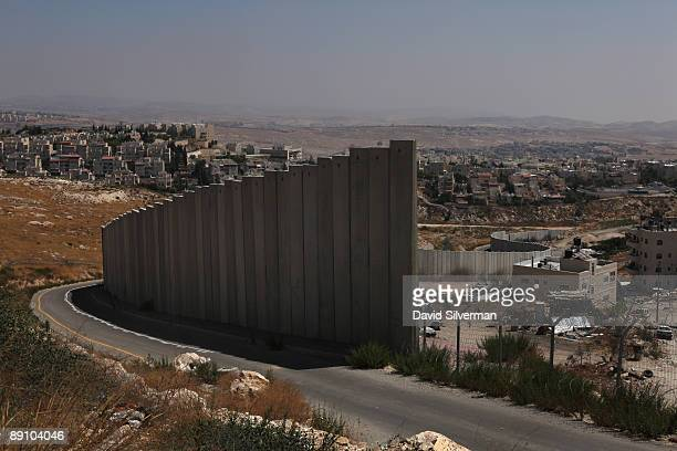 Israel's controversial West Bank barrier weaves its way between the Palestinian refugee camp of Shuafat and the Jewish neighbourhood of Pisgat Zeev...