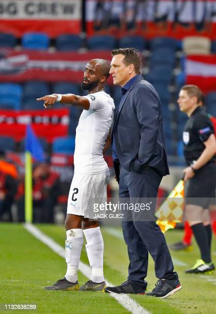Israel's defender Eli Dasa speaks with his coach Andi Herzog during the Euro 2020 Group G football qualification match between Israel and Austria at...
