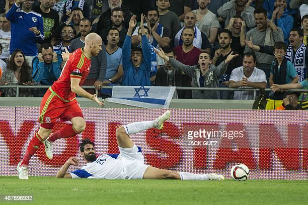 Israel's defender Omri Ben Harush falls following a challenge from Wales' defender James Collins during the Euro 2016 qualifying football match...