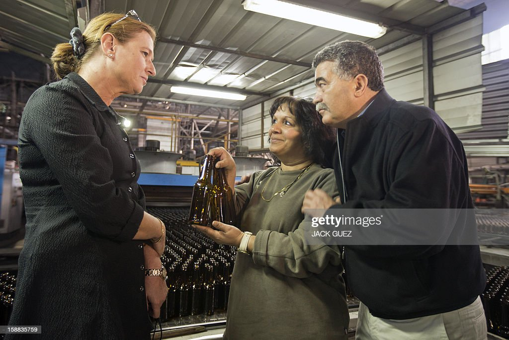 Israel's former foreign minister and chairman of a new party called The Movement, Tzipi Livni (L), speaks with workers as she visits a factory of glass bottles during her campaign rally in the southern city of Yeruham, south of Beer Sheva, on December 31, 2012. Livni announced her return at the helm of The Movement party, nearly seven months after she stepped aside following a primary defeat.